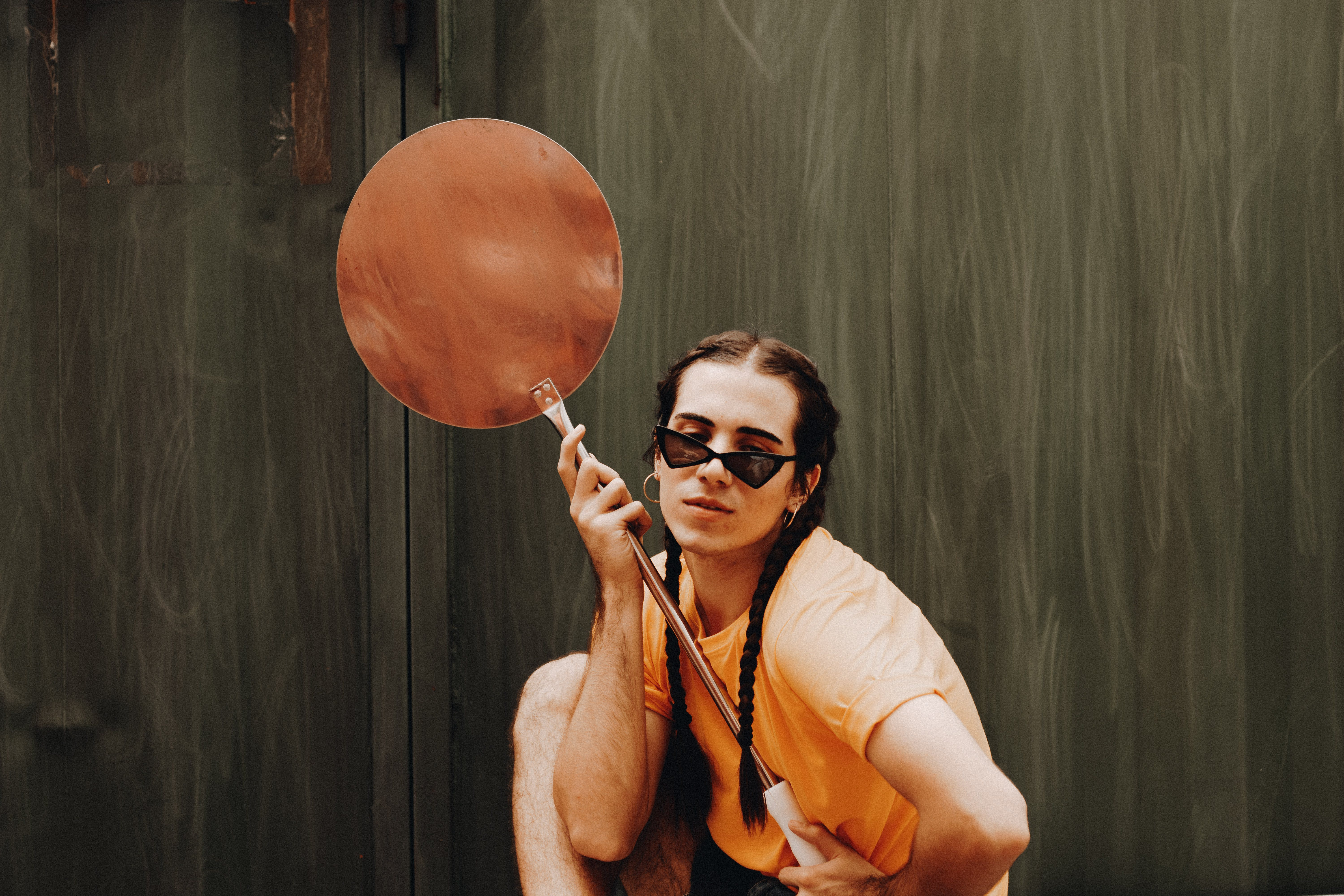 Photo of Man in Orange T-shirt Holding Metal Object