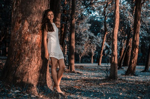 Woman iI White Lace Dress Standing Beside Tree