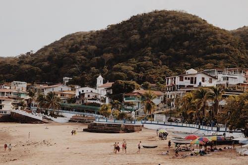 People on Seashore Near Houses
