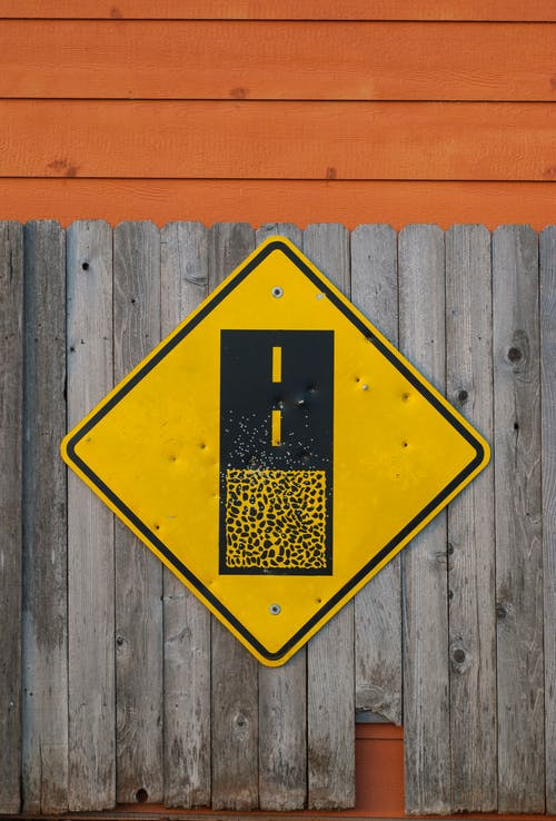 Yellow and Black Road Sign on Gray Wooden Fence