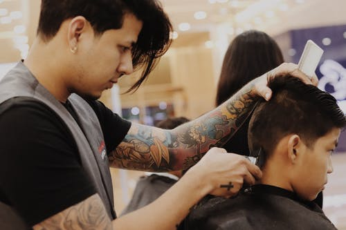 Barber Using Hair Trimmer On Boy's Hair