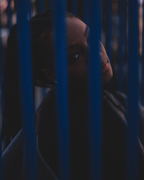 Woman Behind Blue Bars