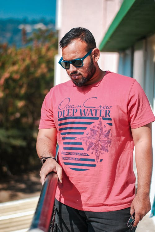 Shallow Focus Photo Of Man In Red Crew Neck T-shirt Wearing Sunglasses
