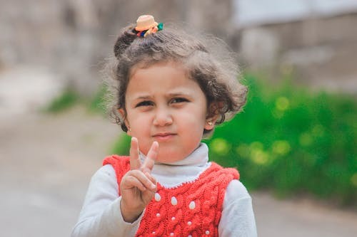 Portrait Photo of Small Girl Standing Doing Peace Sign