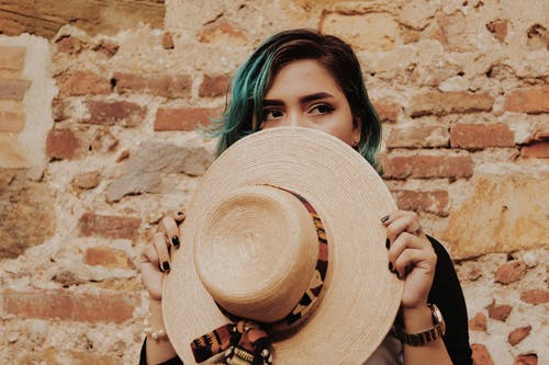 Photo of Woman Covering Her Face With Brown Sun Hat Standing In Front of  Brick Wall