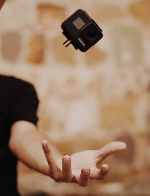 Person Opening Hand About To Catch Gopro Action Camera