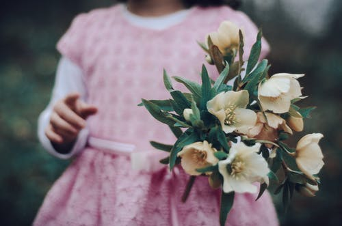 Selective Focus Photo of Girl Holding Flowers