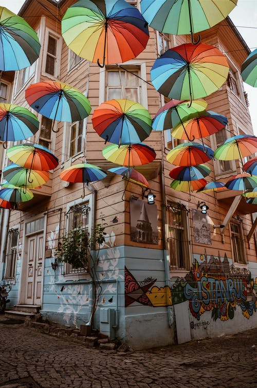 Multicolored Umbrella Hung Outside Brown Wooden House