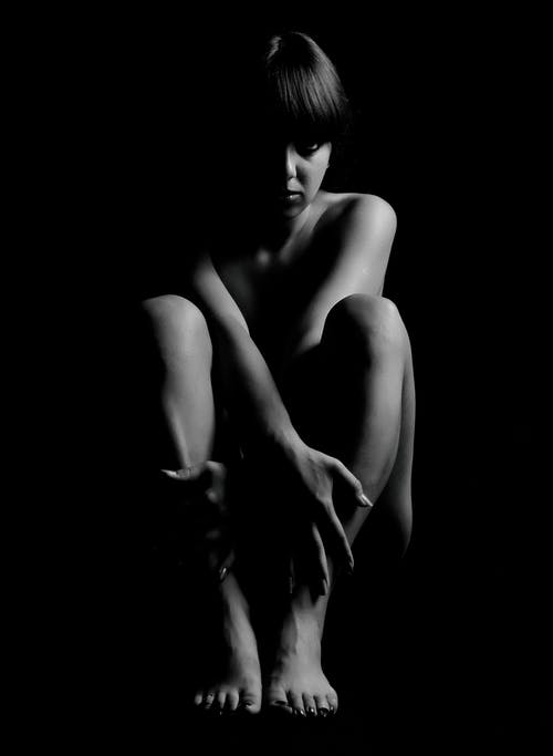 Grayscale Photography Of Woman Inside Dark Room