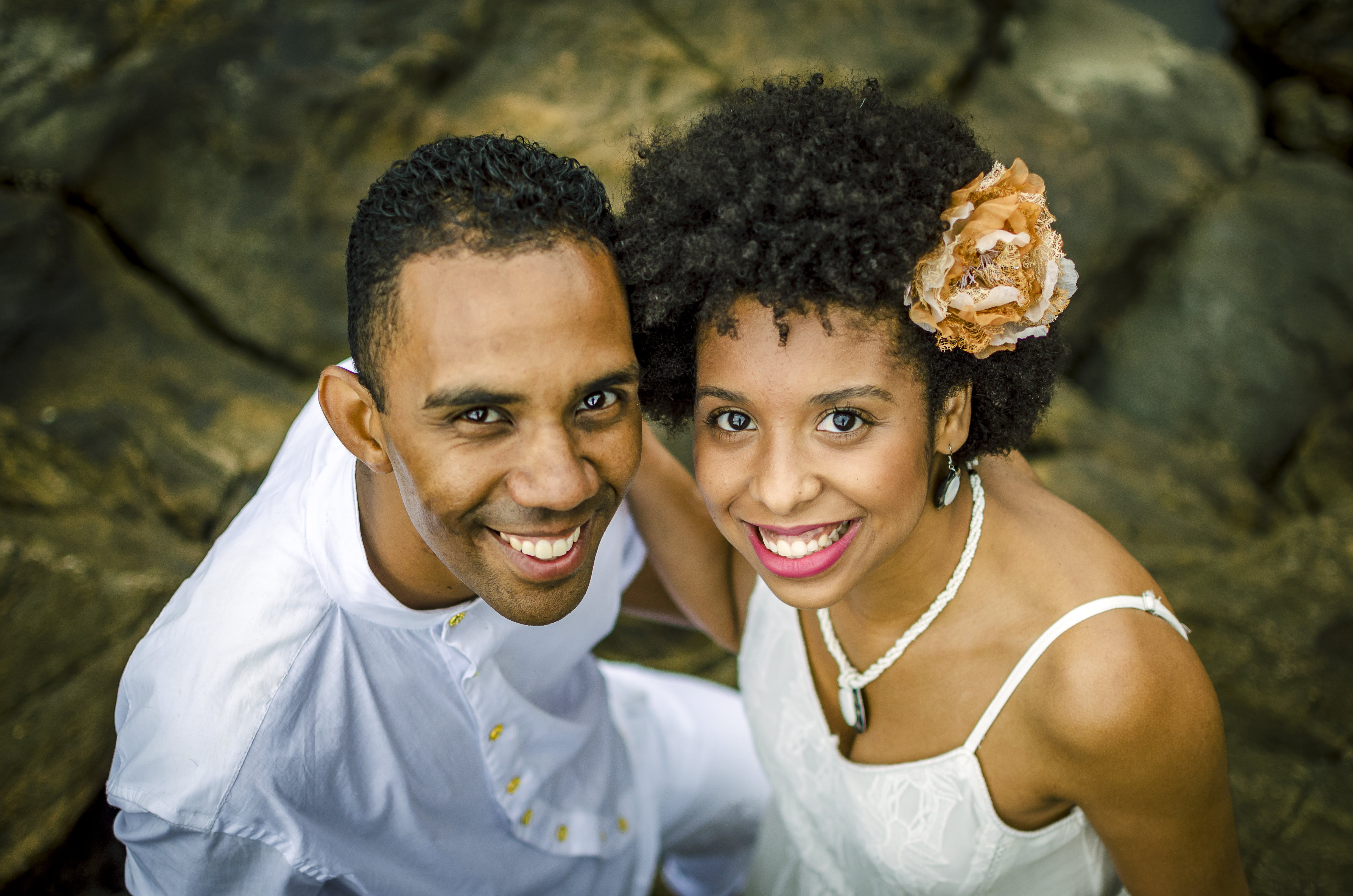 Photo of a Man and Woman Smiling While Standing on Rocks