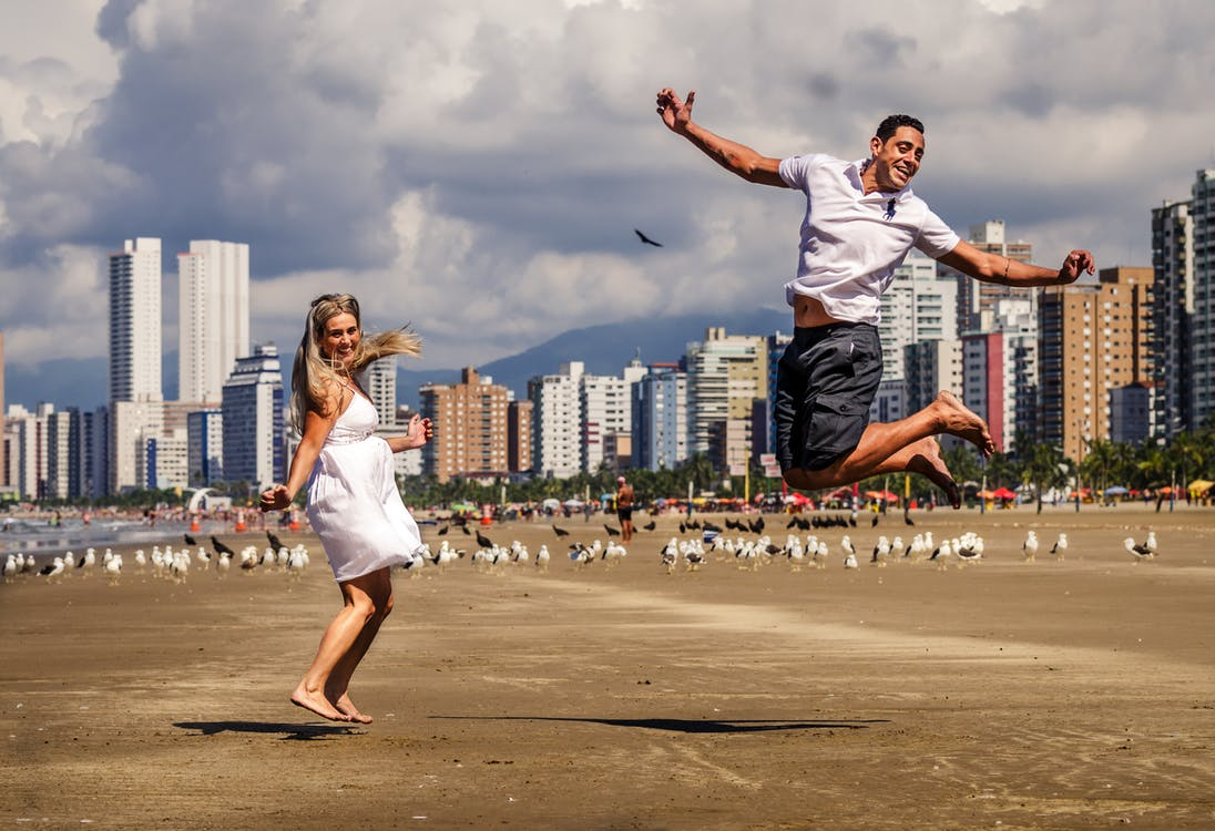 Photo of a Man and A Woman Jumping
