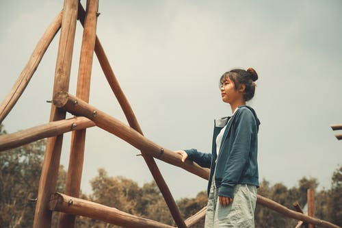 Photo of a Woman Standing Beside Bamboo Post
