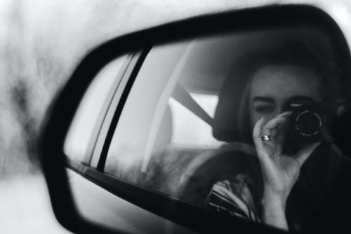Grayscale Photography of Woman Holding Camera Shooting at Vehicle Side Mirror