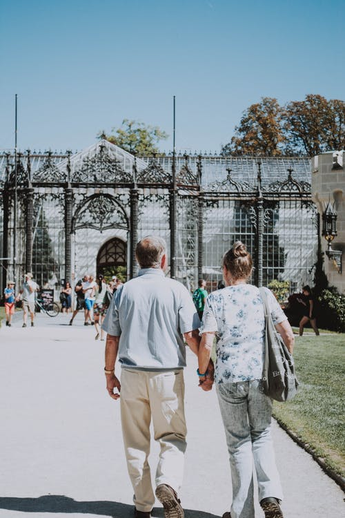 Man and Woman Walking on Pavement