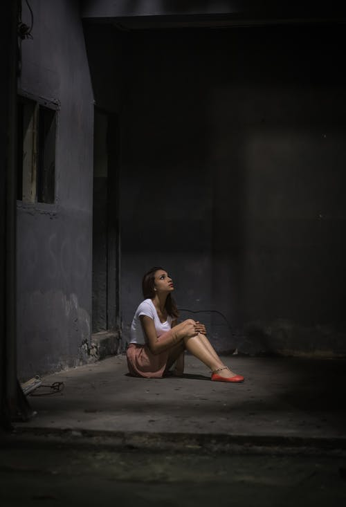 Lonely woman on concrete floor hugging knees in dungeon