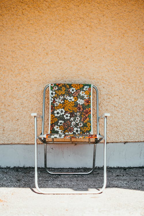 Yellow and Gray Floral Armchair Near Wall