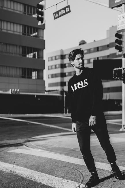 Man in black and whiten long sleeved shirt in grayscale photography