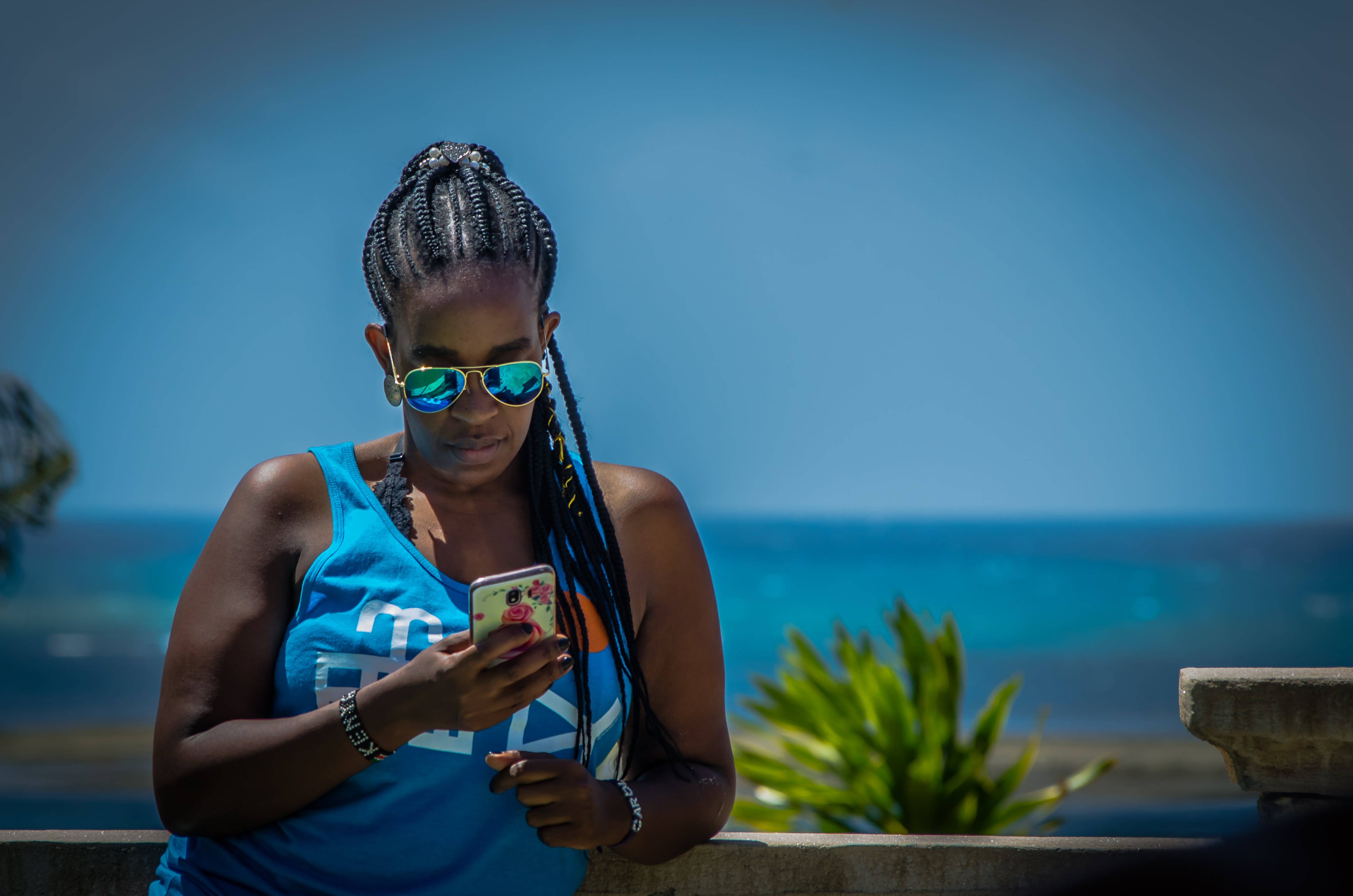Free stock photo of african american woman, beach hotel, blue, braided hair