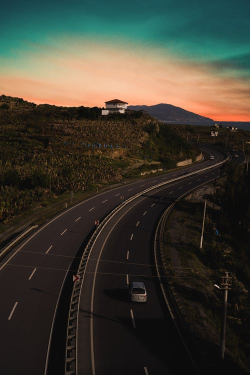 Grey Car Traveling on Swerving Highway Under Green and Orange Sky