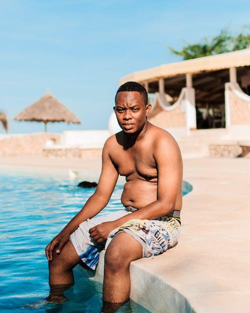 Man Sitting Beside Pool