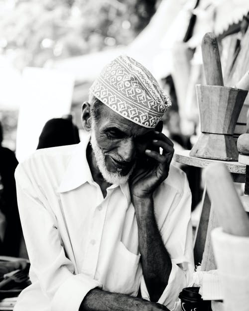 Grayscale Photo of Man Taking Call
