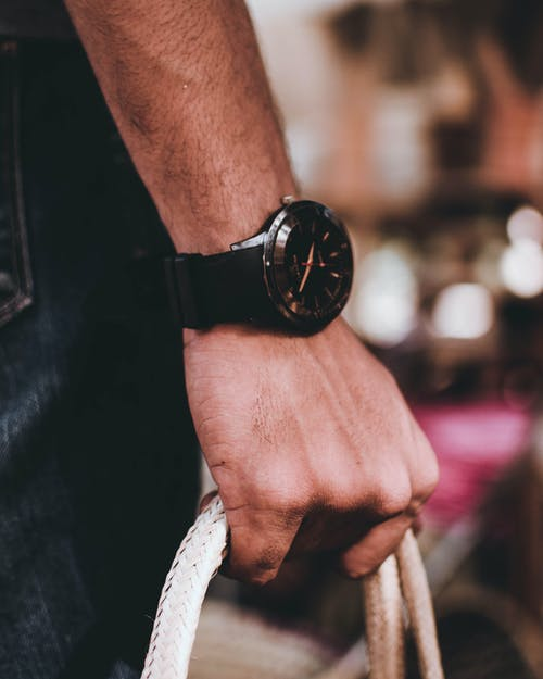 Man Wearing Black Wristwatch Holding Bag