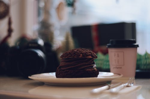 Plate of Chocolate Dessert Beside Coffee Cup and Dslr Camera