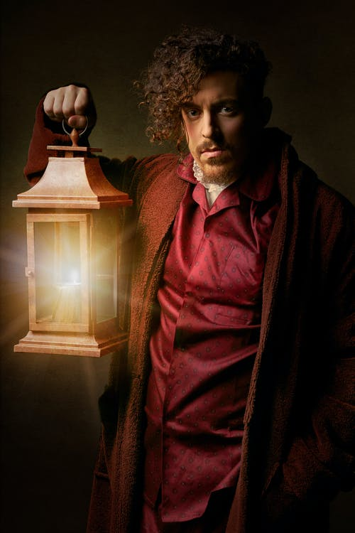 Person Wearing Brown Coat Holding Brown Candle Lamp