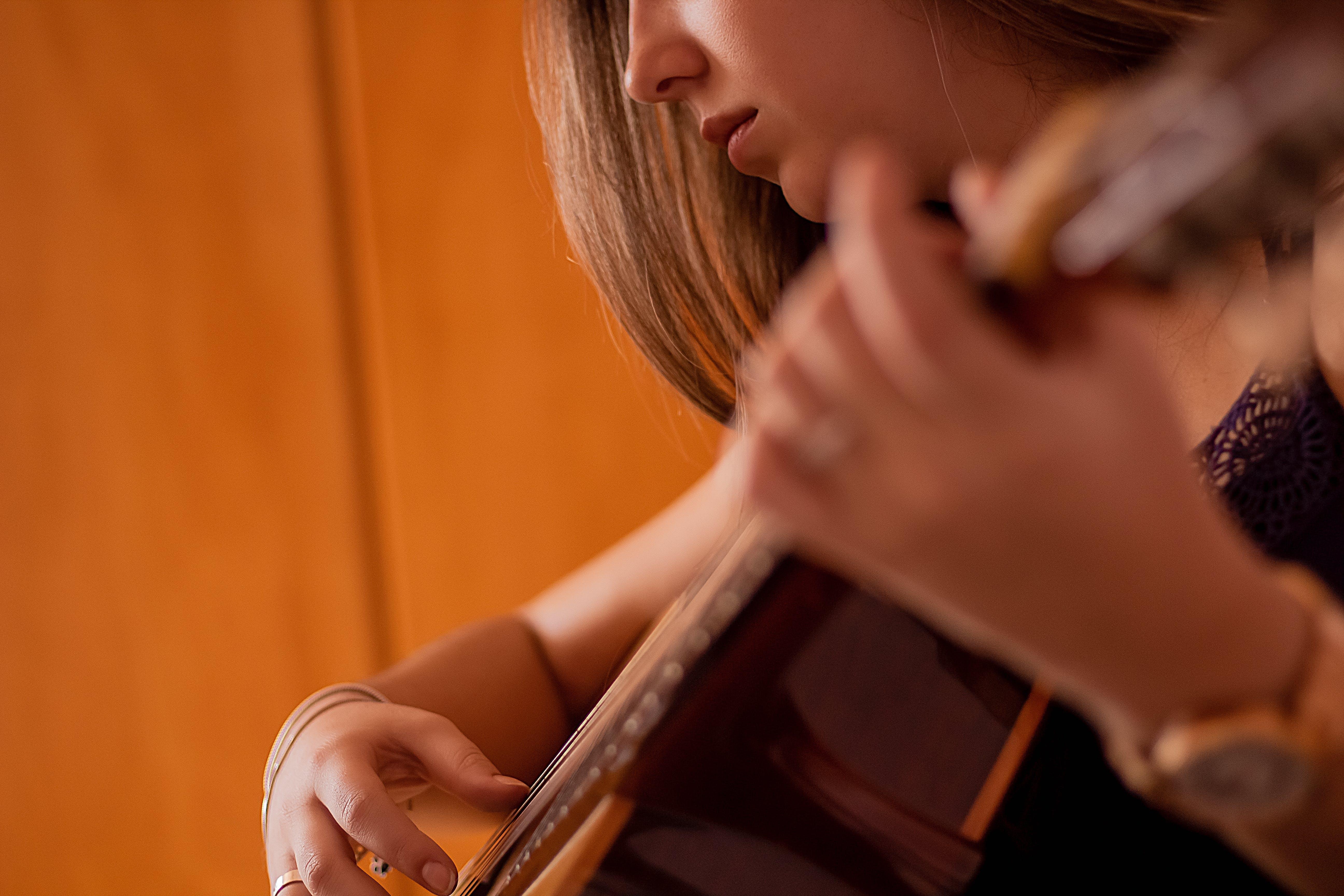 Kostenloses Stock Foto zu akustische gitarre, fokus, frau, gitarre