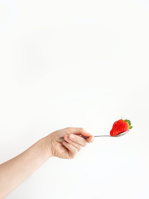 Person Holding Spoon With Strawberry