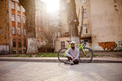 Man Sits on Pavement Near Green Rigid Bike