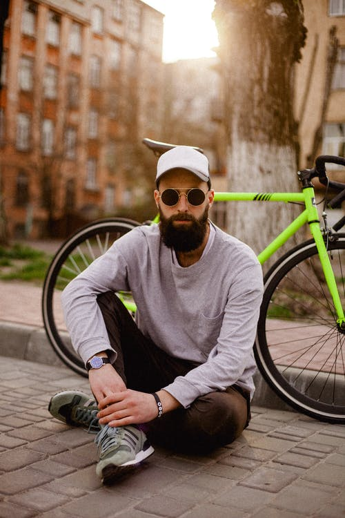 Photo of Man Sitting Near Bike
