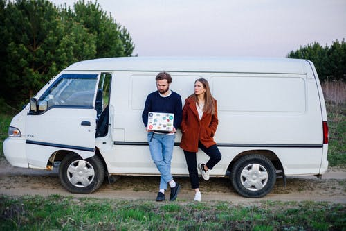 Woman and a man leaning on a White Van