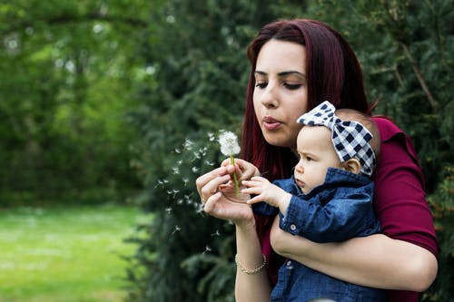 Woman Holding Baby While Blowing Dandelion