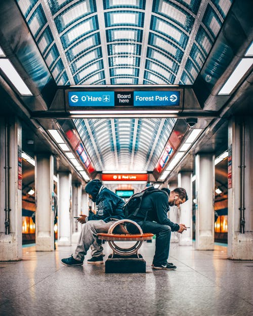 Two Men Sitting On Bench Inside A Station