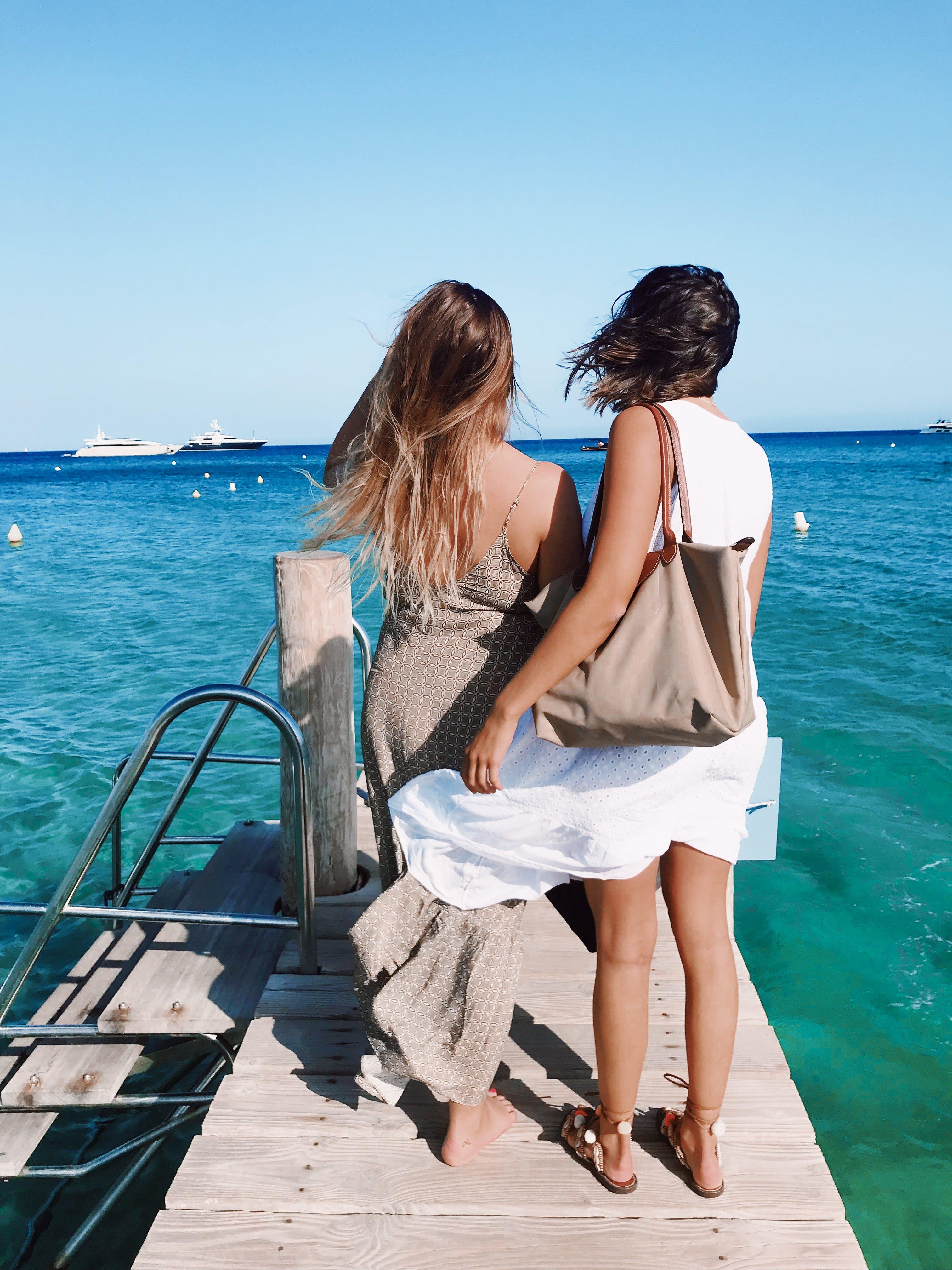 Two Women Standing on Wooden Footbridge Above the Sea