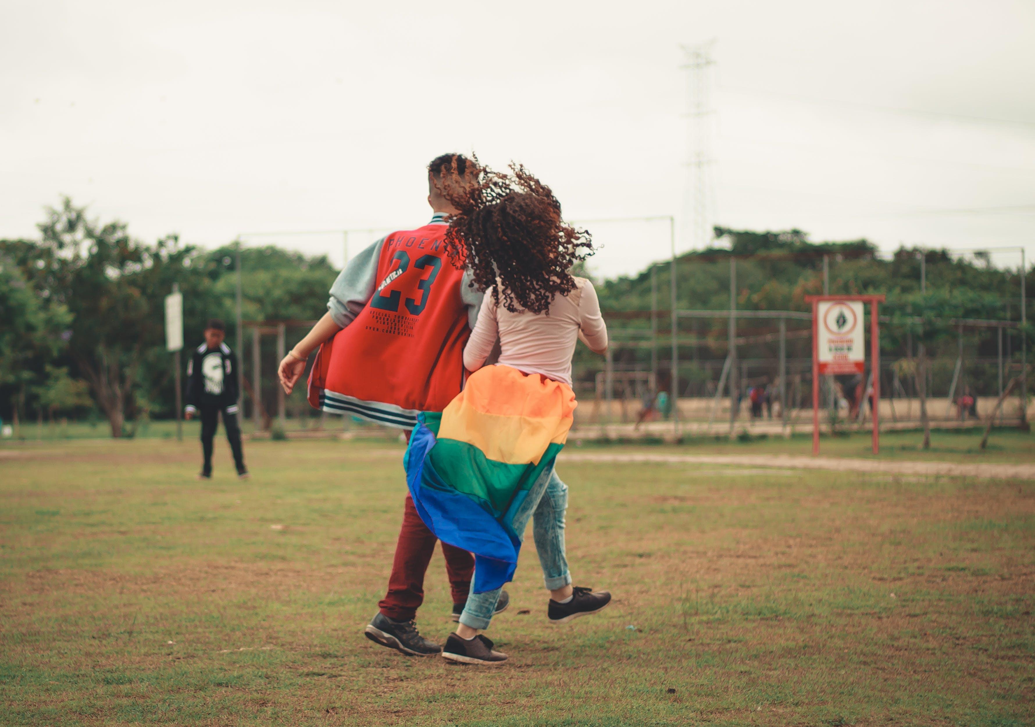 Základová fotografie zdarma na téma chůze, denní světlo, dvojice, fotbalové hřiště