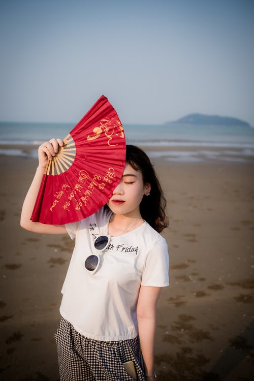 Photo of Woman Standing at the Beach Holding Hand Fan Hiding Part of Her Face