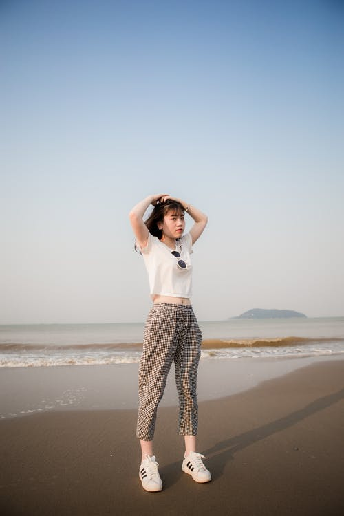 Woman Wearing White Shirt Standing on Sand