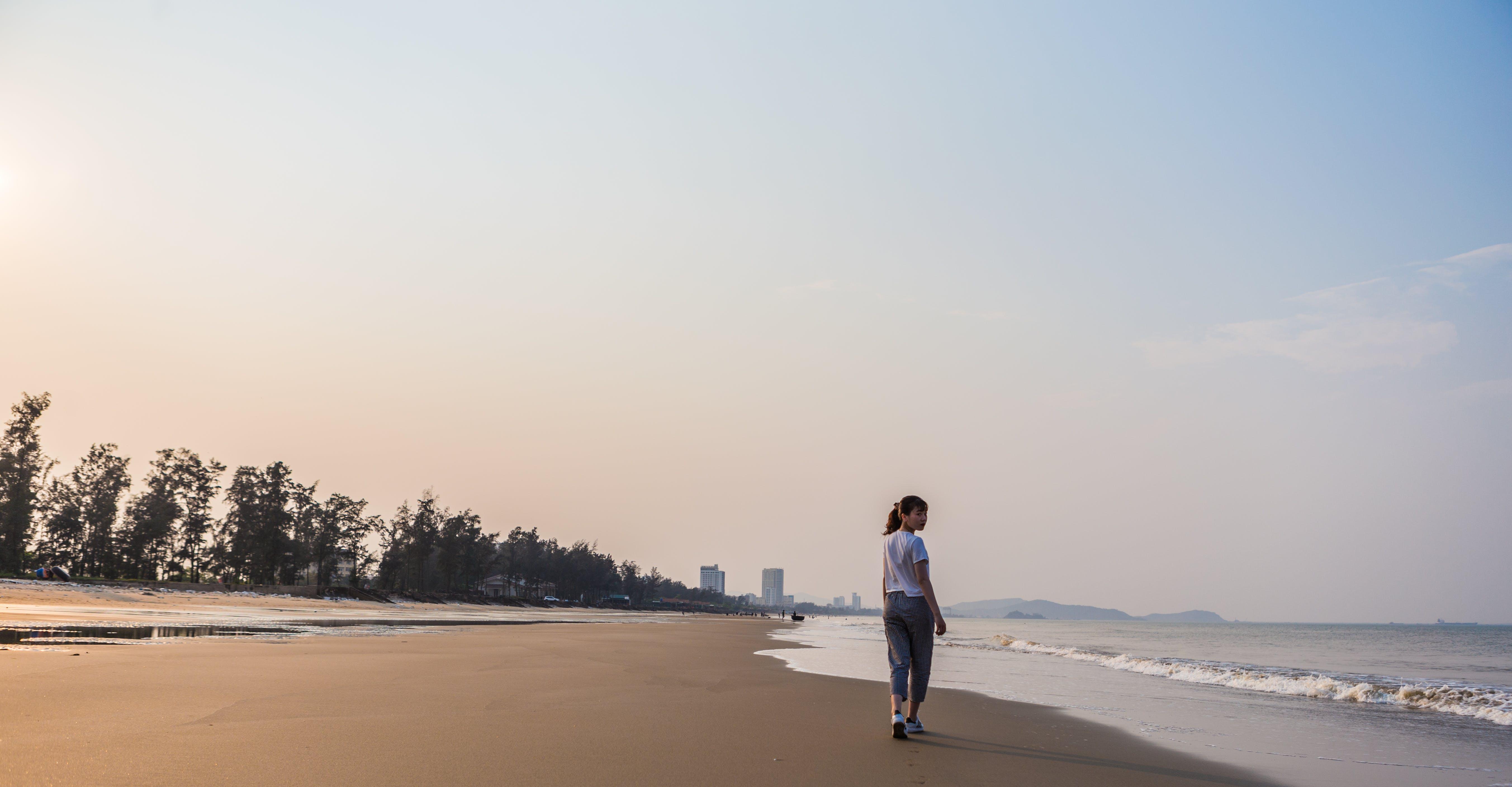 Woman Walking on Shore Near Body of Water