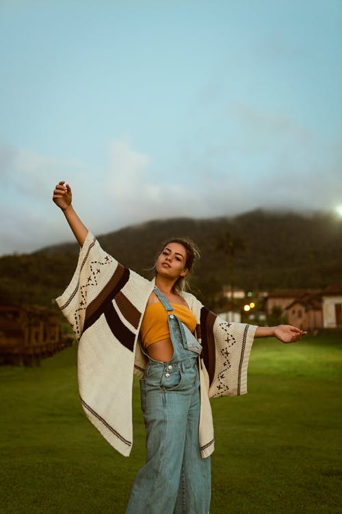 Photo of Woman Wearing Orange Crop Top and Dungaree Pants Posing With Her Hands Raised