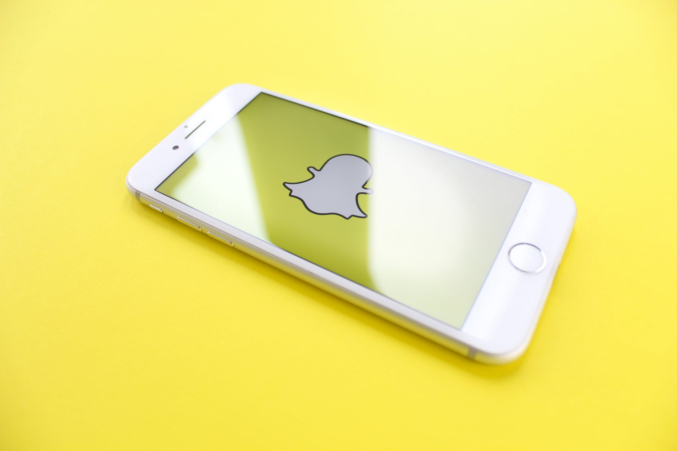 White smartphone with Snapchat logo on yellow background pros and cons of Instagram