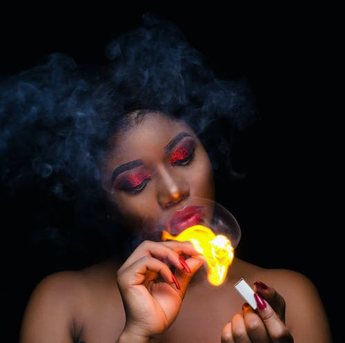 Photo of a Woman Holding Match Stick with Fire