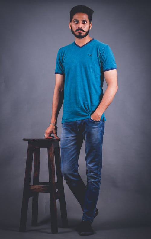 Photo of Man Standing Beside Wooden Stool