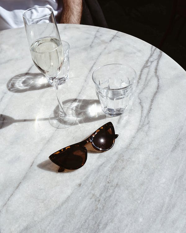 Brown Framed Sunglasses Near Two Drinking Glasses