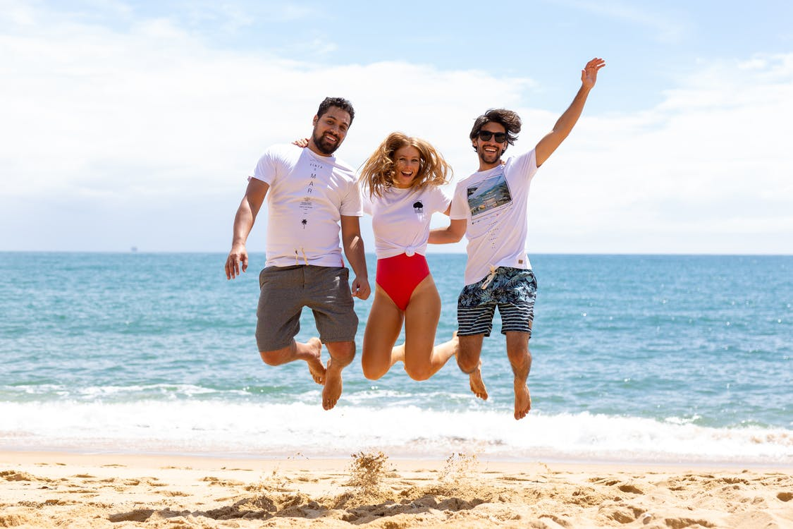 Two Men and One Woman Jumping Near Shore