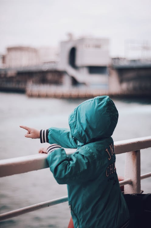 Toddler Wearing Green Hooded Jacket Pointing Right Index Finger