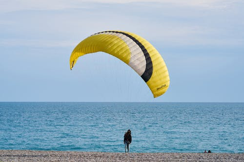 Person With Yellow and White Gliding Parachute Near Sea