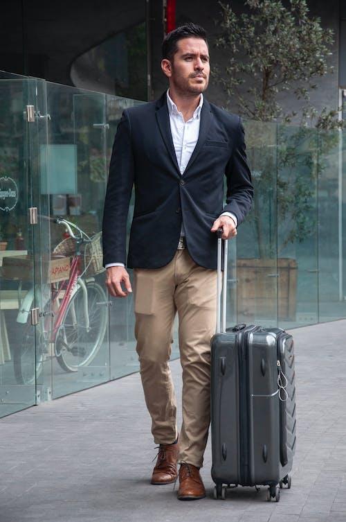 Man Standing On Sidewalk While Holding Luggage Bag