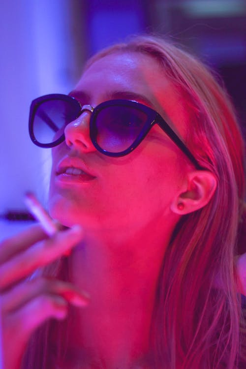 Close-up Photo of Woman in Sunglasses Smoking a Cigarette